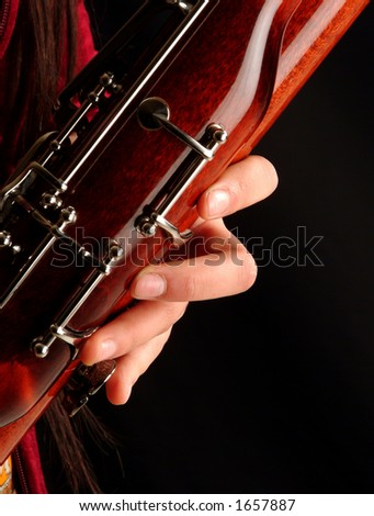 Close up to a hand playing bassoon - stock photo