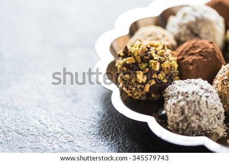 Close up to homemade chocolate praline with pistachios in the plate,selective focus - stock photo