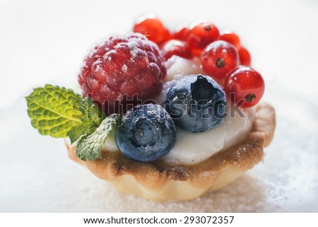 Close up to mini tart stuffed with vanilla pudding and berry fruits,selective focus - stock photo
