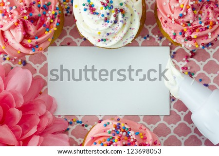Close-up top view of a empty placard with strawberry cupcakes and icing bag. - stock photo