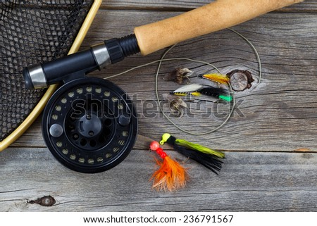 Close up top view of a fishing fly reel, with line, landing net and assorted flies, and partial cork handled pole on rustic wooden boards   - stock photo