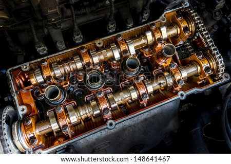 Close up top view of engine parts headers pistons block and chain gear. - stock photo