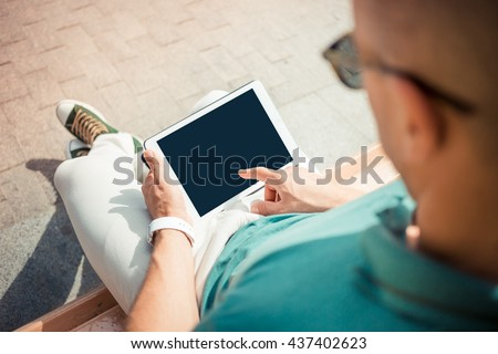 Close-up top view of man holding digital tablet while sitting outdoors. business person browsing internet or connecting to wireless via touchscreen pad - stock photo