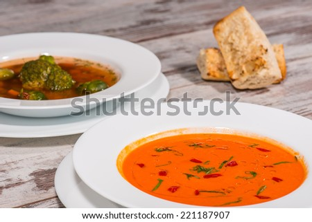 Close-up top-view picture of cold tasty tomato soup gazpacho with species and one more vegan soup on the wooden table in vegan caffee with tasty buns standing near a plate, with copy place  - stock photo
