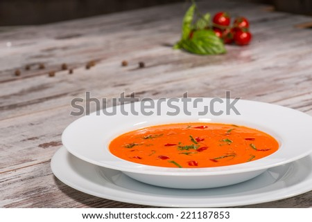 Close-up top-view picture of cold tasty tomato soup gazpacho with species on the wooden table in vegan caffee with tomatoes standing near a plate, with copy place and selective focus on a plate - stock photo