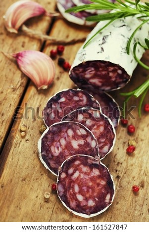 Close-up traditional sliced meat sausage salami on wooden board with head of garlic and green herbs  - stock photo