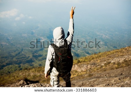 Close-up travel image,of hiker man posing on the mountain,hands up,freedom concept ,peace sign.man in cross country trail run.Fit male climbing outdoors in beautiful mountain nature landscape Iceland. - stock photo
