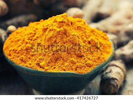 Close up Turmeric powder on wooden background  - Vintage Filter Processing. - stock photo