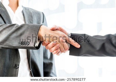 Close up Two Businessmen in Suit Showing Hand Shake Gesture Inside the Office. - stock photo
