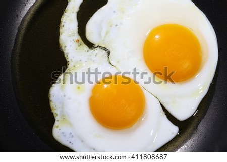 close up two fried eggs on black pan - stock photo