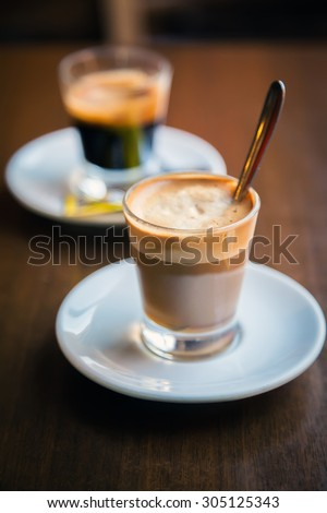 close-up two glasses of coffe - espresso and macchiato - stock photo