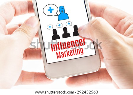 Close up Two hand holding smart phone with Influencer Marketing word and icons, Digital concept. - stock photo