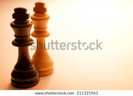 Close up Two Standing Wooden King Chess Pieces, Isolated on Light Brown Background. - stock photo