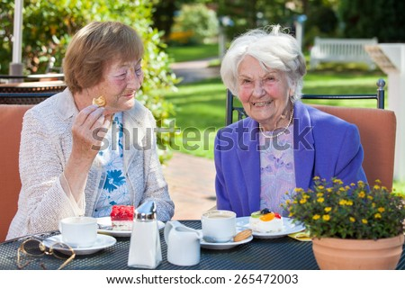 Close up Two Stylish Cheerful Elderly Women Relaxing at the Outdoor Table with Coffee and Snacks - stock photo