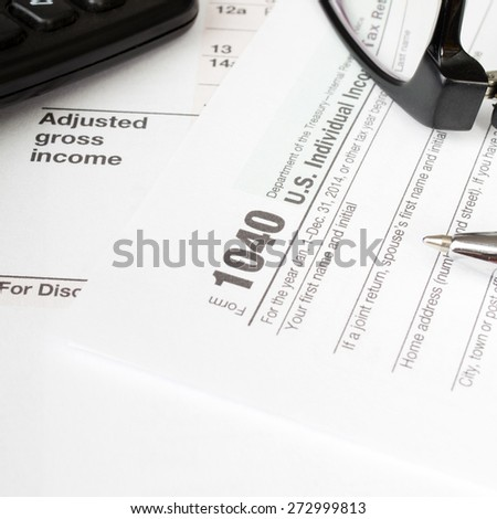 Close up U.S. Individual tax form 1040 with, glasses, calculator and pen. - stock photo