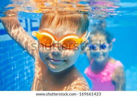 Close-up underwater portrait of the cute smiling boy - stock photo