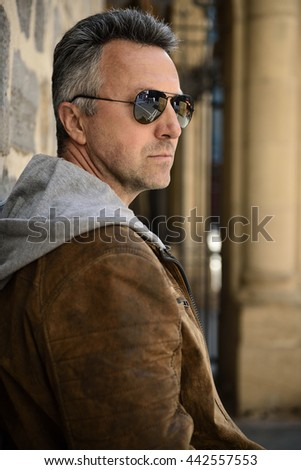 Close-up urban outdoor portrait of a handsome man with sunglasses, image toned and noise added.  - stock photo