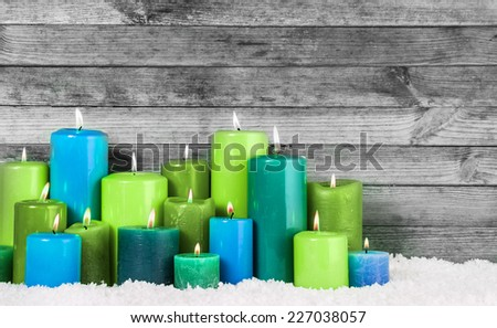Close up Various Blue and Green Lighted Christmas Candles in Snow with Vintage Wall Background. - stock photo