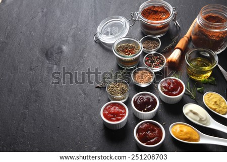 Close up Various Condiments on Containers and Spoons on Top of Black slate Table with Copy Space on the Left Side. - stock photo