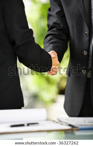Close up vertical portrait of two businessman handshaking, East Asian skin tone - stock photo