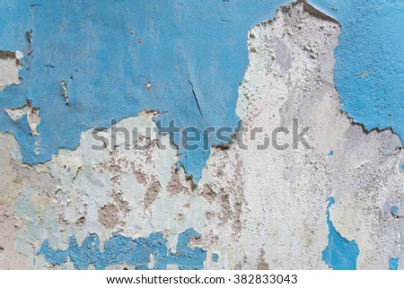 Close-up view a weathered damaged concrete wall with blue peeling paint and cracked stucco layer. Pattern of rustic blue grunge material from old wall seamless texture in an ancient town of Vietnam. - stock photo