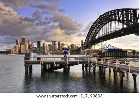 Close up view from wooden ferry pier to distant Sydney City CBD skyscrapers and arch of Harbour Bridge near sunset - stock photo