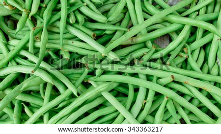 Close-up view group of fresh small, slender wax green beans (or string beans, haricot vert) on display at Vegetable Stall of Local Market, Little India, Singapore. Colorful food ingredient background  - stock photo