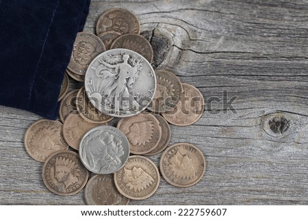 Close up view of a bag of United States vintage coins spilling out onto rustic wood - stock photo
