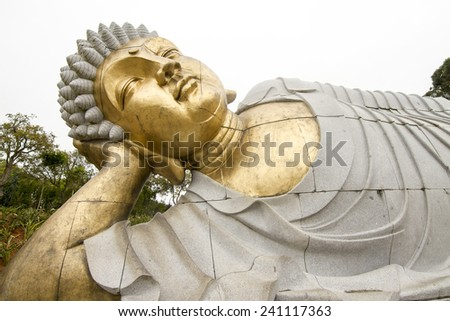 Close up view of a beautiful reclining  Buddha statue on a park. - stock photo
