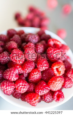Close up view of a beautiful selection of freshly picked ripe red raspberries in the white bowl on a metal background, selective focus, shallow depth of field - stock photo