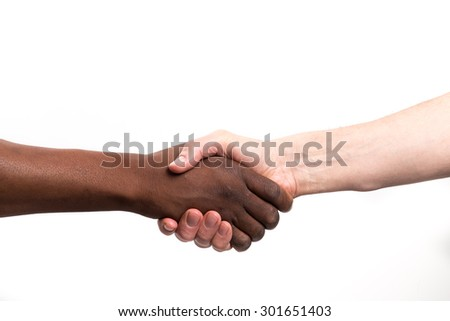 Close up view of a black / african man and a white / caucasian man shaking hands - stock photo