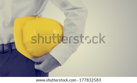 Close up view of a businessman carrying a yellow hardhat under his arm, retro effect faded look with copyspace. - stock photo