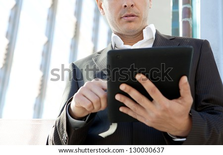 Close up view of a businessman using a digital technology tablet pad while standing in a modern office building in the city. - stock photo