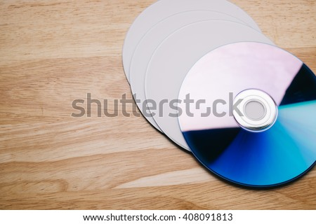 Close up view of a CD/DVD on wood table, vintage tone - stock photo