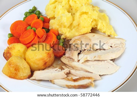 Close-up view of a chicken dinner with roast potatoes, mixed vegetables, mashed potato and gravy. - stock photo