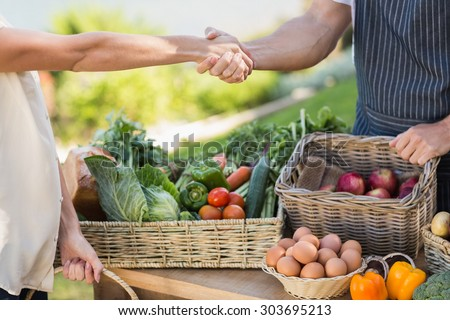 Close up view of a farmer and customer shaking hands - stock photo