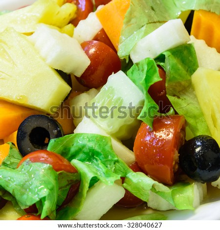 Close-up view of a fresh dish of mixed organic fruits salad with pineapple, cucumber, apple, cherries tomatoes, lettuce, carrot, olive. Colorful and healthy concept - stock photo