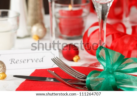 Close up view of a holiday table setting with red and green decorations and placard showing a reserved space - stock photo