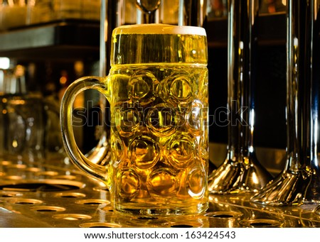 Close up view of a large glass tankard of draught beer standing on a bar counter at the foot of the stainless steel beer taps for dispensing the draft - stock photo