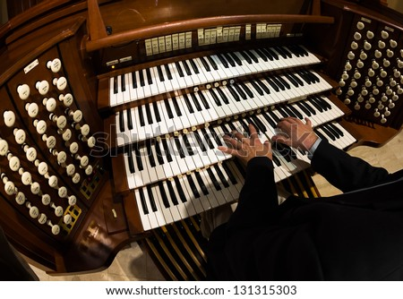Close up view of a organist playing a pipe organ. - stock photo