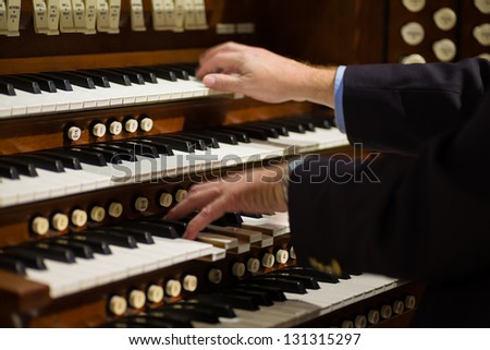 Close up view of a organist playing a pipe organ with motion blur. - stock photo