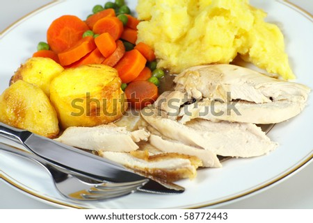 Close-up view of a roast chicken dinner and cutlery, comprising sliced chicken breast, roast potatoes, mixed vegetables, mashed potato and gravy - stock photo
