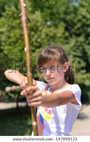 Close up view of a young girl practising her archery taking aim with a homemade bow and arrow in a park - stock photo
