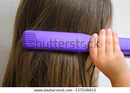 Close up view of a young girl straightening her hair - stock photo