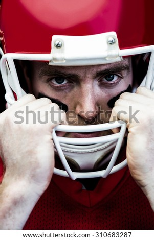 Close up view of american football player holding onto his helmet - stock photo