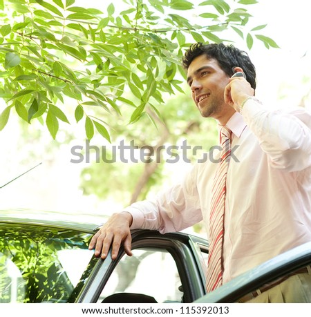 Close up view of an attractive businessman with his car having a phone conversation using a hands free set in a tree lined street in the city. - stock photo