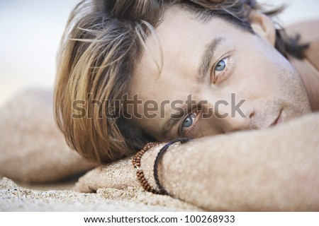Close up view of an attractive young man laying down on a white sand beach. - stock photo