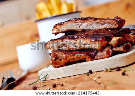 Close up view of barbecue ribs with fries and sauce on a old wooden table - stock photo