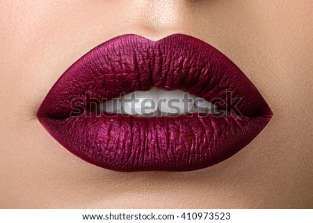 Close up view of beautiful woman lips with purple matt lipstick. Open mouth with white teeth. Cosmetology, drugstore or fashion makeup concept. Beauty studio shot. Passionate kiss - stock photo