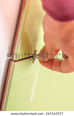Close up view of bottom spacers being used by a tiler while tiling a wall to ensure an even gap for the grout between the tiles in a DIY and renovation concept.  - stock photo